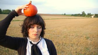 Girld holding hokkaido pumpkin on her head (dreaming about autumn/autumn cuisine) in a autumnal colored field (in bavaria, Germany).