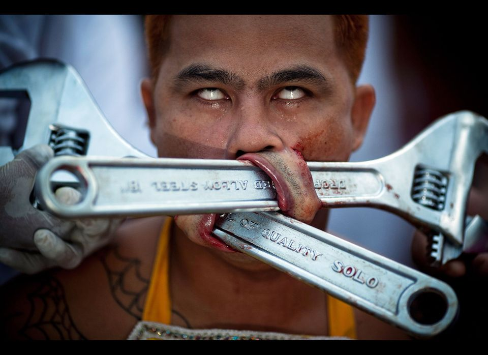 A devotee of the Chinese shrine of Samkong, pierces his cheeks with wrenchs during a procession of Vegetarian Festival on Oct