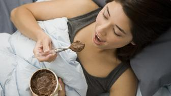 Woman lying in bed eating chocolate ice cream
