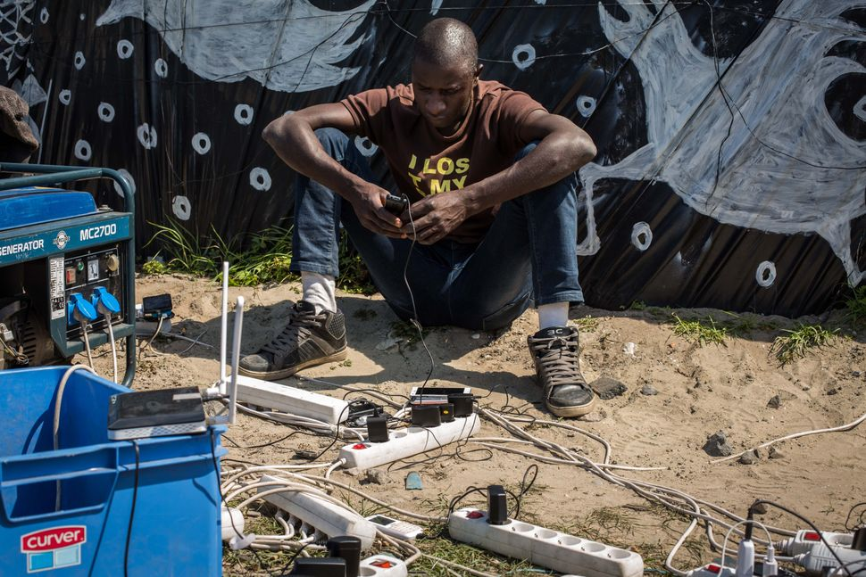 A man uses a generator to charge a mobile phone in a makeshift camp near the port of Calais, France, on Aug. 1, 2015.