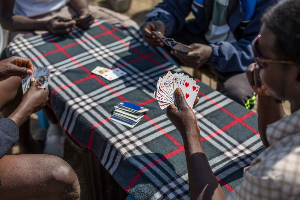 Sudanese men play cards in a makeshift camp near the port of Calais, Aug. 1, 2015.