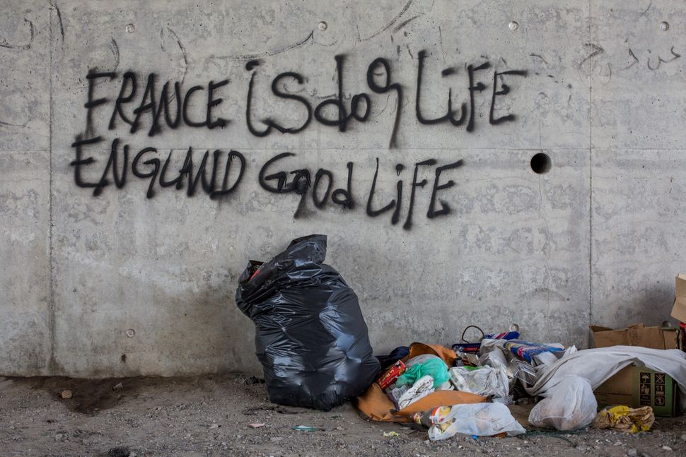 Graffiti reading 'France is dog life, England good life' is seen on a wall close to a makeshift camp near the port of Calais