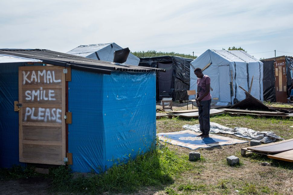 A man prays in a makeshift camp near the port of Calais on Aug. 1, 2015.