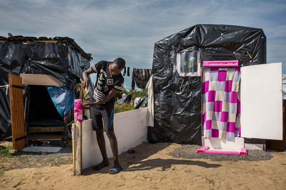 Muher from Sudan adds a dividing wall outside his tent in a makeshift camp near the port of Calais on Aug. 1, 2015.