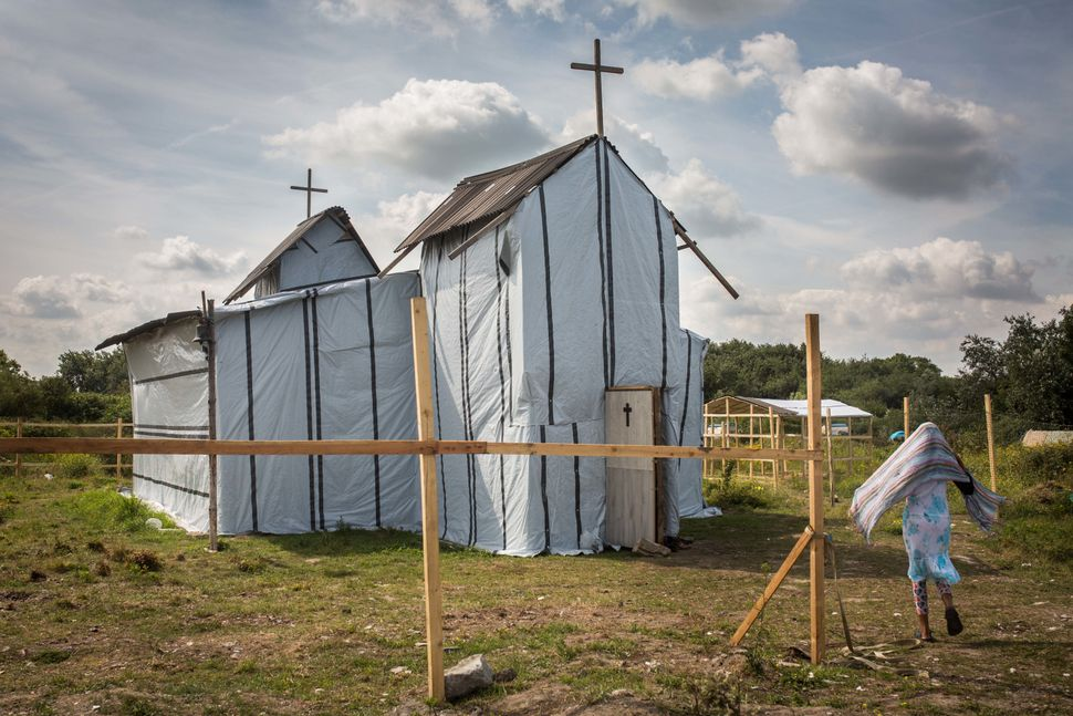 A woman enters the site of a church in a makeshift camp near the port of Calais on July 31, 2015.