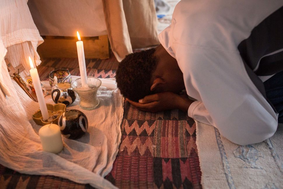 A man prays during an Orthodox service for Ethiopian and Eritrean worshippers at a church in a makeshift camp near the port o