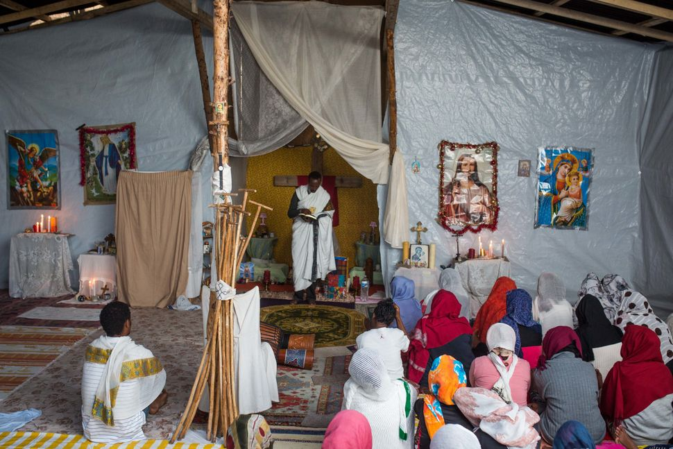 Kibrom Kasta leads an Orthodox service for Ethiopian and Eritrean worshippers at a church in a makeshift camp near the port o