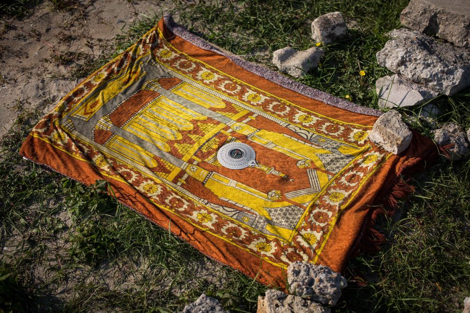 A compass rests on a prayer mat in a makeshift camp near the port of Calais on Aug. 2, 2015.