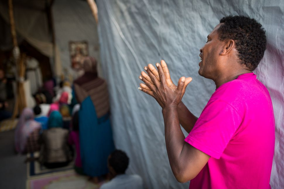 A man sings during an Orthodox service for Ethiopian and Eritrean worshippers at a church in a makeshift camp near the port o