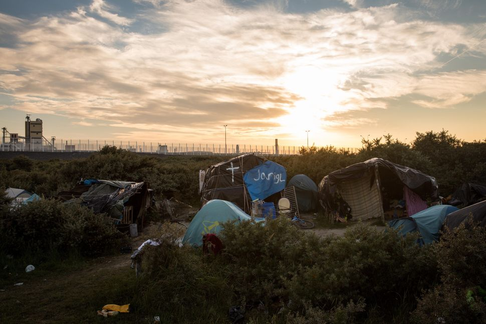 The sun sets behind a makeshift camp near the port of Calais on Aug. 2, 2015.