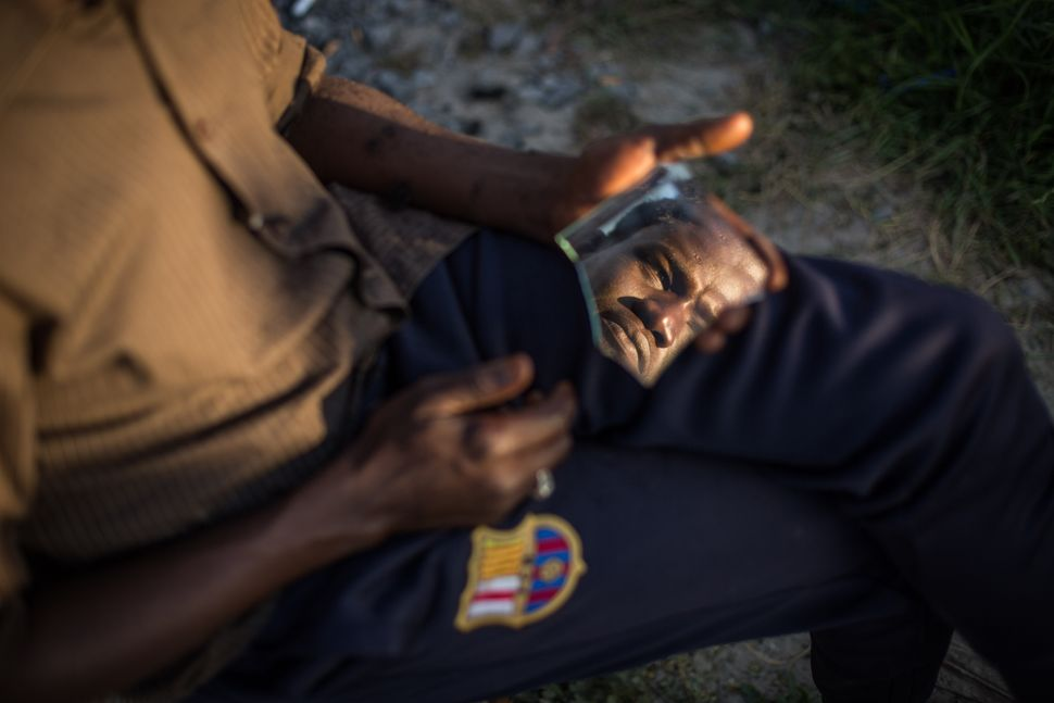 A Sudanese man is seen in a piece of broken mirror whilst having his hair cut in a makeshift camp near the port of Calais on
