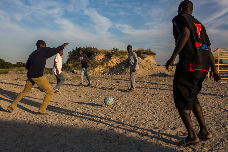 Men play football in a makeshift camp near the port of Calais on Aug. 2, 2015.