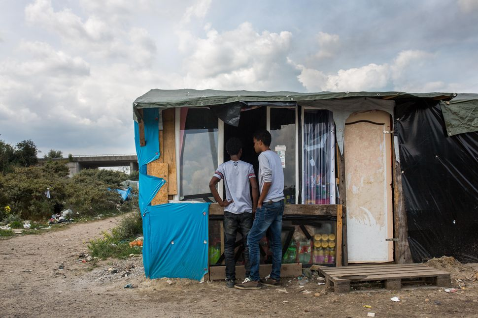 Men buy from a shop run by Afghanis at a makeshift camp near the port of Calais on July 31, 2015.