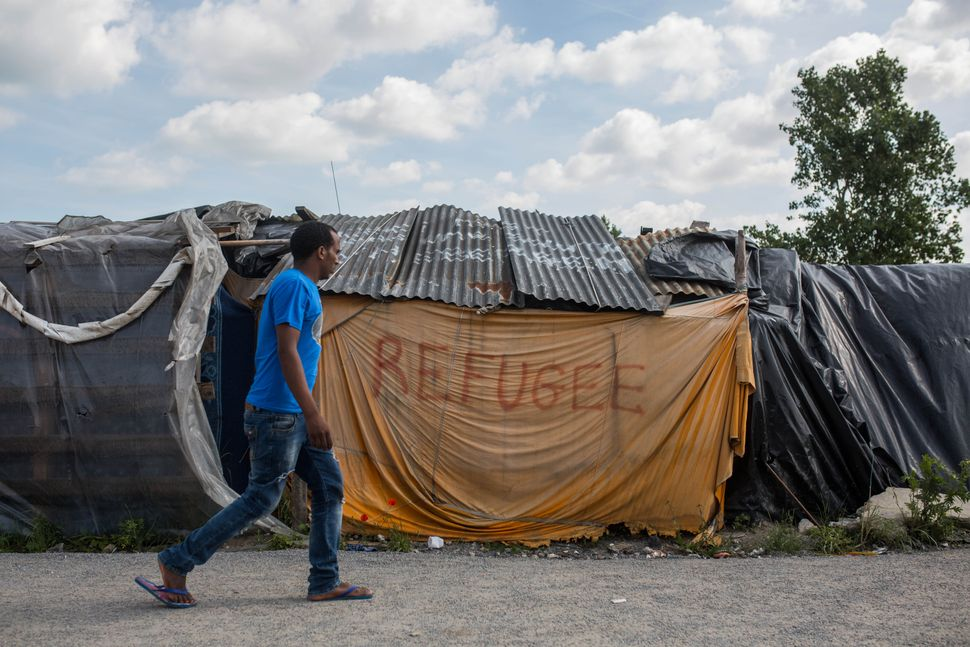 A man walks past a tent in a makeshift camp near the port of Calais on July 31, 2015.