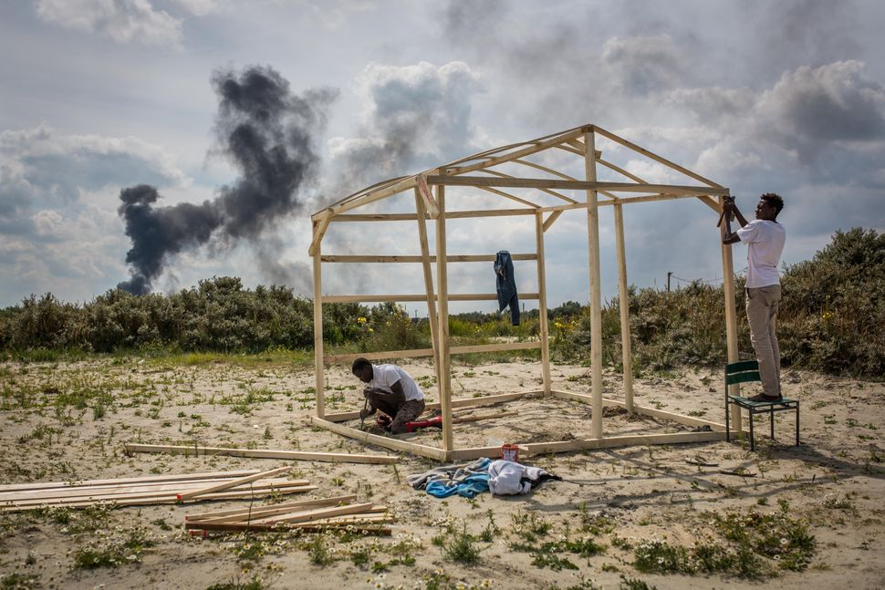 Gamal and Sabry from Sudan build a wooden structure at a make shift camp near the port of Calais on July 31, 2015.