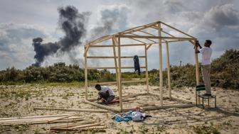 CALAIS, FRANCE - JULY 31:  Gamal and Sabry from Sudan build a wooden structure at a make shift camp near the port of Calais on July 31, 2015 in Calais, France.  Strike action and daily attempts by hundreds of migrants to enter the Channel Tunnel and onto trains heading to the United Kingdom is causing delays to passenger and freight services across the channel.  British Prime Minster David Cameron has announced that extra sniffer dogs and fencing are to be sent to Calais and land owned by the Ministry of Defence is to be used as a lorry park to ease congestion near the port of Dover in Kent. (Photo by Rob Stothard/Getty Images)