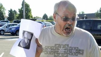 Tom Sullivan holds up a photo of his son Alex Sullivan pleading the media to help find him, outside Gateway High School a few blocks from the scene of the Century 16 Theatre shootings in Aurora, Colorado July 20, 2012.