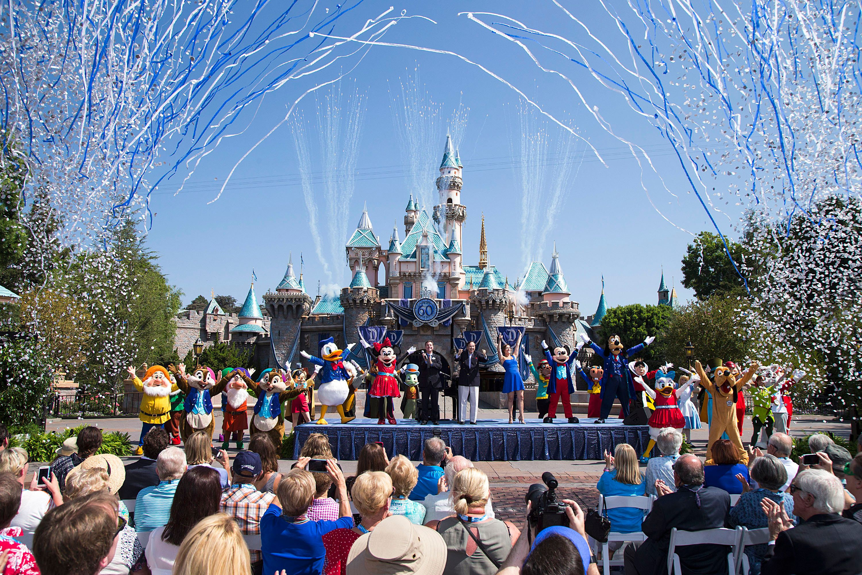 ANAHEIM, CA - JULY 17:  In this handout photo provided by Disney parks, Mickey Mouse and his friends celebrate the 60th anniversary of Disneyland park during a ceremony at Sleeping Beauty Castle featuring Academy Award-winning composer, Richard Sherman and Broadway actress and singer Ashley Brown July 17, 2015 in Anaheim, California.  Celebrating six decades of magic, the Disneyland Resort Diamond Celebration features three new nighttime spectaculars that immerse guests in the worlds of Disney stories like never before with 'Paint the Night,' the first all-LED parade at the resort; 'Disneyland Forever,' a reinvention of classic fireworks that adds projections to pyrotechnics to transform the park experience; and a moving new version of 'World of Color' that celebrates Walt Disneys dream for Disneyland.  (Photo by Paul Hiffmeyer/Disneyland Resort via Getty Images)