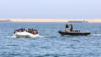 Libyan coast guards escort a boat carrying illegal migrants, who had hoped to set off to Europe with the help of people smugglers from the coastal town of Garabulli, towards the Libyan navy to the capital, Tripoli, prior to their arrest on June 6, 2015. Libya has a coastline of 1,770 kilometres (more than 1,000 miles). It is just 300 kilometres from the Italian island of Lampedusa, which many migrants fleeing poverty and conflict aim for as their gateway to Europe. AFP PHOTO / MAHMUD TURKIA        (Photo credit should read MAHMUD TURKIA/AFP/Getty Images)