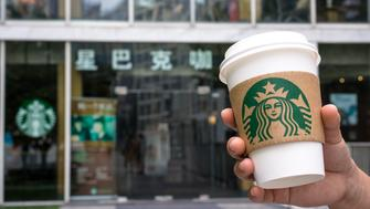 BEIJING, CHINA - 2015/07/27: Hand holding a coffee cup outside a Starbucks shop in Beijing Jianwai Soho.  Starbucks reported a higher-than-expected revenue and 7 percent global same-store-sales growth, which includes an 11 percent increase in the China/Asia Pacific market.  Now the company has more than 1,700 stores in more than 90 cities in mainland China, with the entire APAC region operating more than 5,200 stores. (Photo by Zhang Peng/LightRocket via Getty Images)