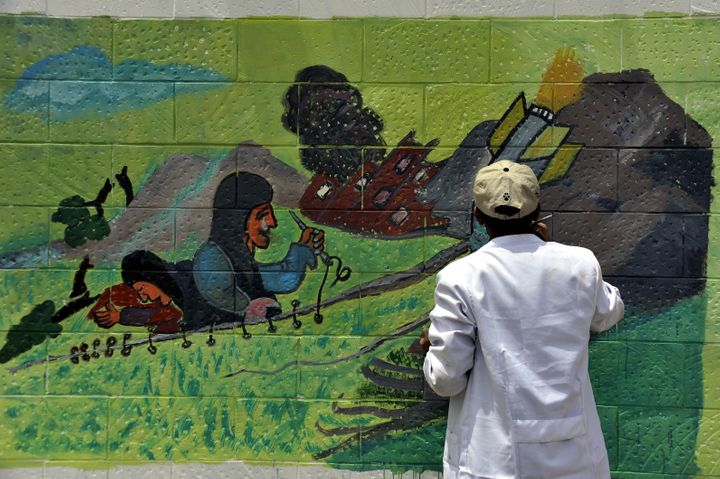 A Yemeni graffiti artist paints a mural protesting the airstrikes on the exterior wall of the Saudi Arabian Embassy in Sanaa,