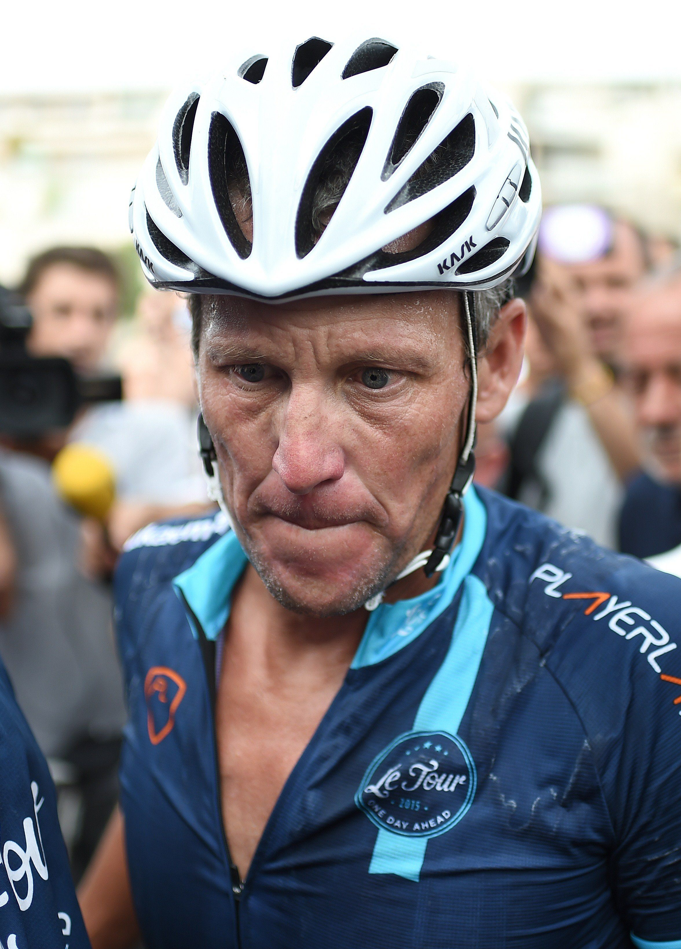 US cyclist Lance Armstrong looks on upon his arrival in Rodez, southwest France, after riding a stage  of The Tour De France for a leukaemia charity, a day ahead of the competing riders, on July 16, 2015. For the first time since he was stripped of his seven Tour de France titles, disgraced cyclist Lance Armstrong rode a stage of the famous race for charity. Armstrong, 43, was riding a 198-kilometre (123-mile) stage a day ahead of the competing riders for a leukaemia charity but cycling officials have branded the exercise 'disrespectful'. AFP PHOTO / STEPHANE DE SAKUTIN        (Photo credit should read STEPHANE DE SAKUTIN/AFP/Getty Images)