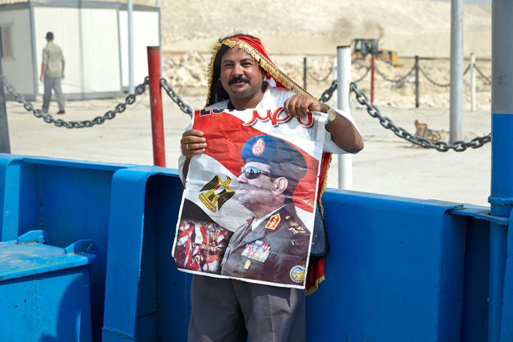 <span>A man wears an Egyptian flag and holds a poster of Egyptian President Abdel Fattah al-Sisi beside a section of the New