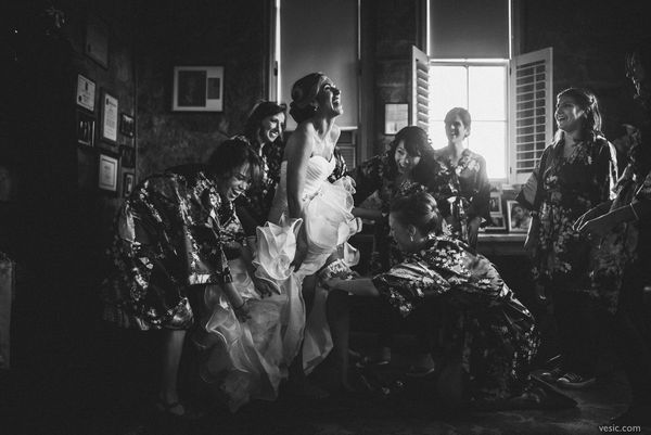"""""""One of my favorite photos is this one of Lera and her bridesmaids helping her get ready. The lighting enhances what is"""