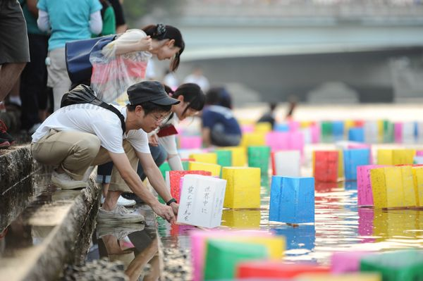 People take part in the Peace Message Lantern Floating Ceremony, held to console the souls of atomic bombing victims, at the
