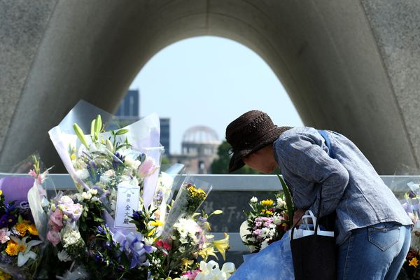 A woman places flowers by a monument at the Hiroshima Peace Memorial Park in Japan on Aug. 5, 2015.
