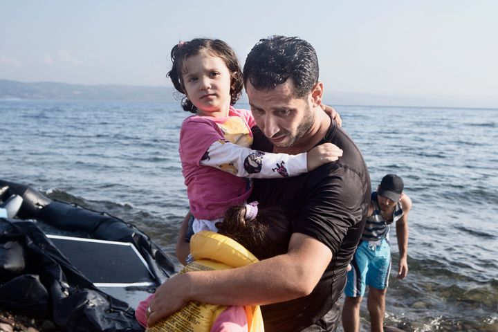 A Syrian father holds his two daughters after their boat lands on Aug. 2, 2015 near Molyvos, on the island of Lesvos, Greece.