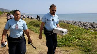 Police officers leave the scene with container holding metallic debris found on a beach in Saint-Denis on the French Reunion Island in the Indian Ocean on August 2, 2015, close to where where a Boeing 777 wing part believed to belong to missing flight MH370 washed up last week.  A piece of metal was found on La Reunion island, where a Boeing 777 wing part believed to belong to missing flight MH370 washed up last week, said a source close to the investigation.  Investigators on the Indian Ocean island took the debris into evidence as part of their probe into the fate of Malaysia Airlines flight MH370, however nothing indicated the piece of metal came from an airplane, the source said.  AFP PHOTO / RICHARD BOUHET        (Photo credit should read RICHARD BOUHET/AFP/Getty Images)
