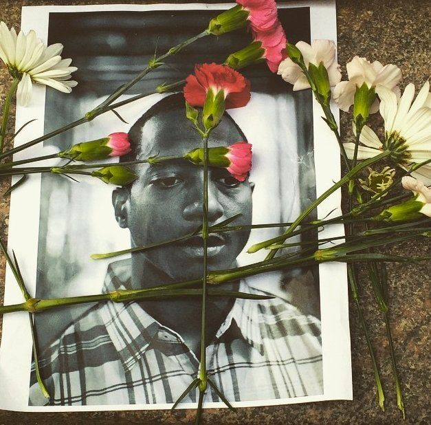 <span>Days after his death, flowers are laid over a photo of Kalief Browder at a vigil outside a Manhattan jail on June 11, 2