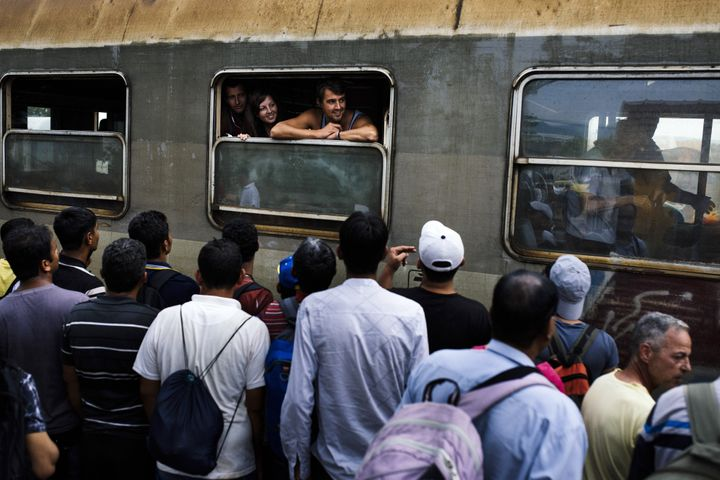 <span>Passengers of the Belgrade-Thessaloniki international train watch migrants waiting to reach a train heading to the Serb