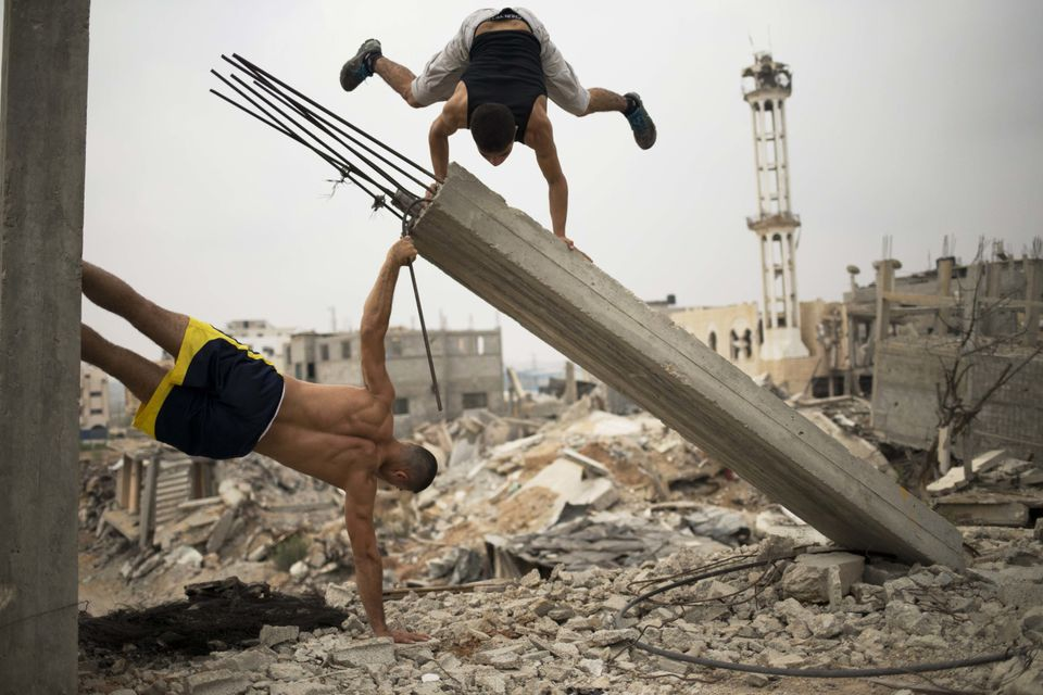 Palestinian group, Bar Palestine, take part in street exercises amid the destruction in Gaza City on August 3, 2015. Street w