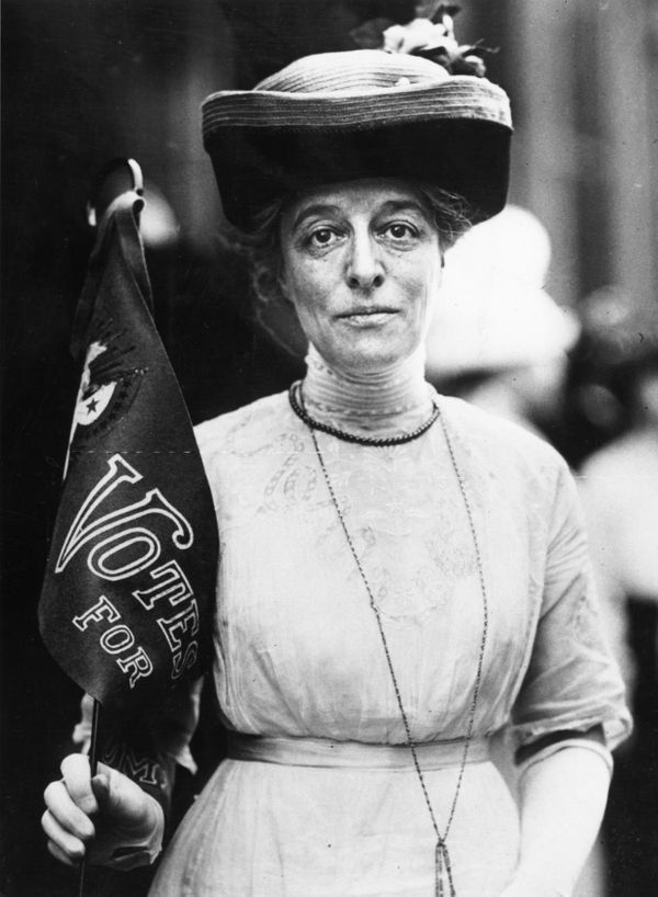 """A suffragette stands with a """"Votes For Women"""" banner in 1910."""