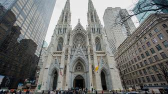 Pedestrians walk past Saint Patrick's Cathedral during a massive restoration effort in New York, U.S., on Tuesday, April 7, 2015. The $180 million project, a first for the 135 year old structure, began in May 2012 and is expected to be finished this year. Photographer: Craig Warga/Bloomberg via Getty Images