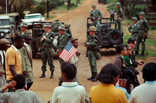 Man with American flag and marchers walking past federal troops guarding crossroads, 1965.