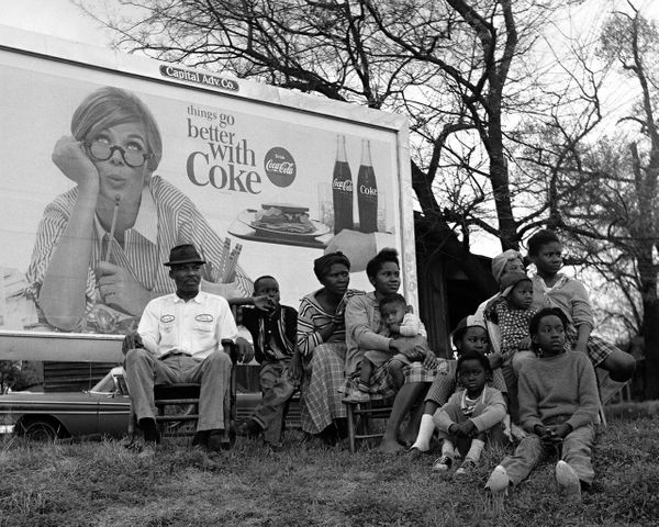 """Things Go Better With Coke"" sign and multi-generational family watching marchers, 1965."