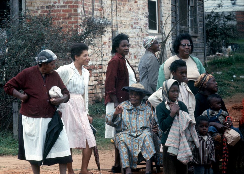 Three generations of women with children watching civil rights marchers, 1965.