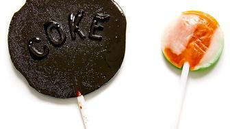 Coke lollipop next to a regular lollipop.