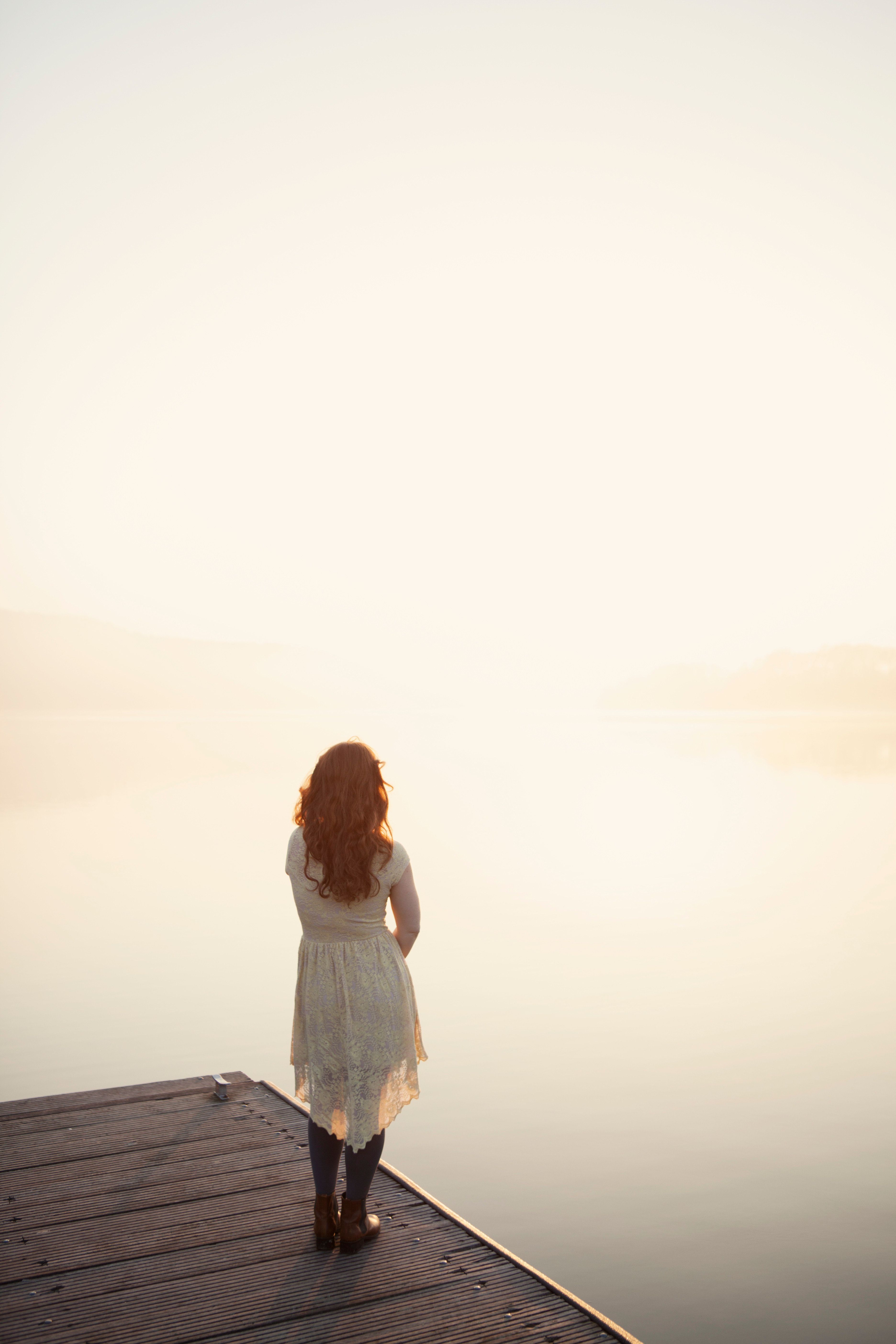 Germany, Essen, Redhead woman looks out onto lake at sunrise