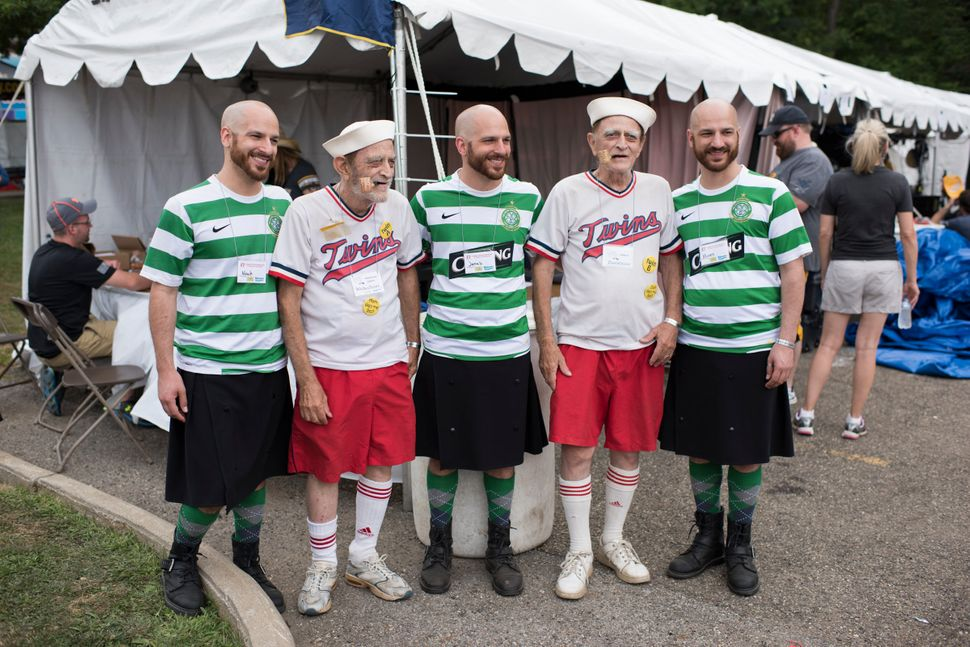 A group of identical twins pose for a portrait with identical triplets at the 40th annual Twins Days Festival in Twinsburg, O