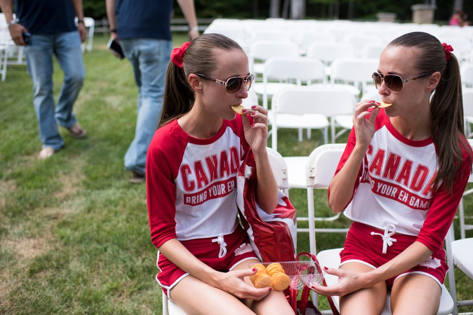 Allison, left, and Lauren Knight, 32 of Windsor, Ontario, share crackers at the Twins Days Festival.