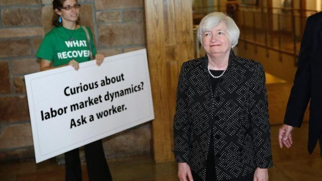 Fed Chair Janet Yellen looks on at a Fed Up activist drawing attention to workers at the Kansas City Fed's 2014 symposium in
