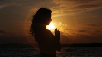 Silhouette of woman with hands in prayer pose at sunrise on beach, lateral view.