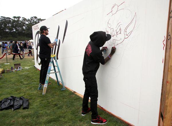 Artists kick off a mural on Saturday.