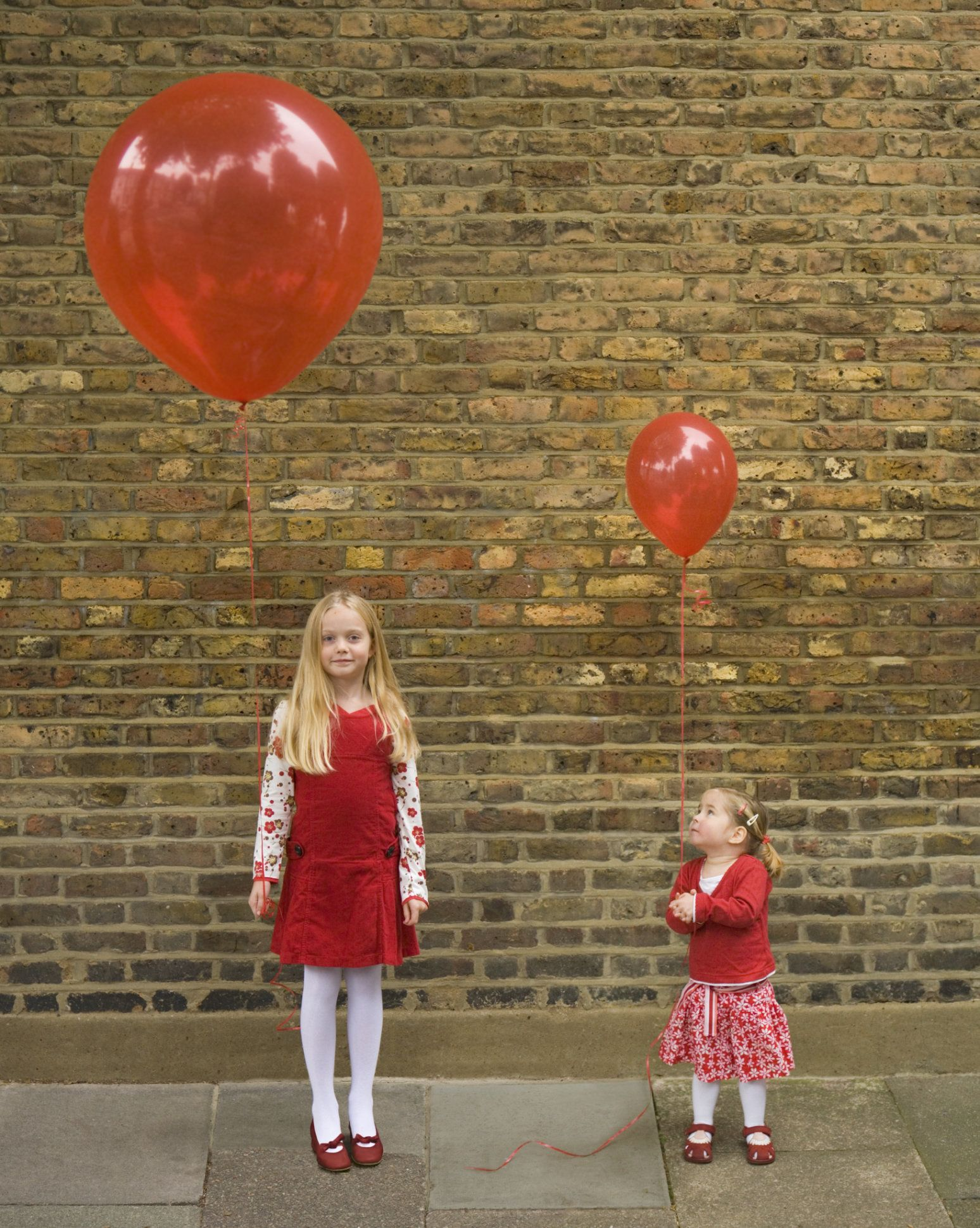 Girl (6-8) and toddler girl (18-24 months) holding balloons
