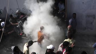 Policemen (rear C) try to disperse hundreds of migrants by spraying them with fire extinguishers during a gathering for a registration procedure at the stadium on the Greek island of Kos, on August 11, 2015. Police on the Greek island on Kos hit migrants with truncheons to prevent a stampede, a day after an officer was caught on camera slapping a migrant. The incident occurred as hundreds of migrants were being relocated to a local football stadium, after camping alongside roads and beaches across the island for weeks. AFP PHOTO / ANGELOS TZORTZINIS        (Photo credit should read ANGELOS TZORTZINIS/AFP/Getty Images)