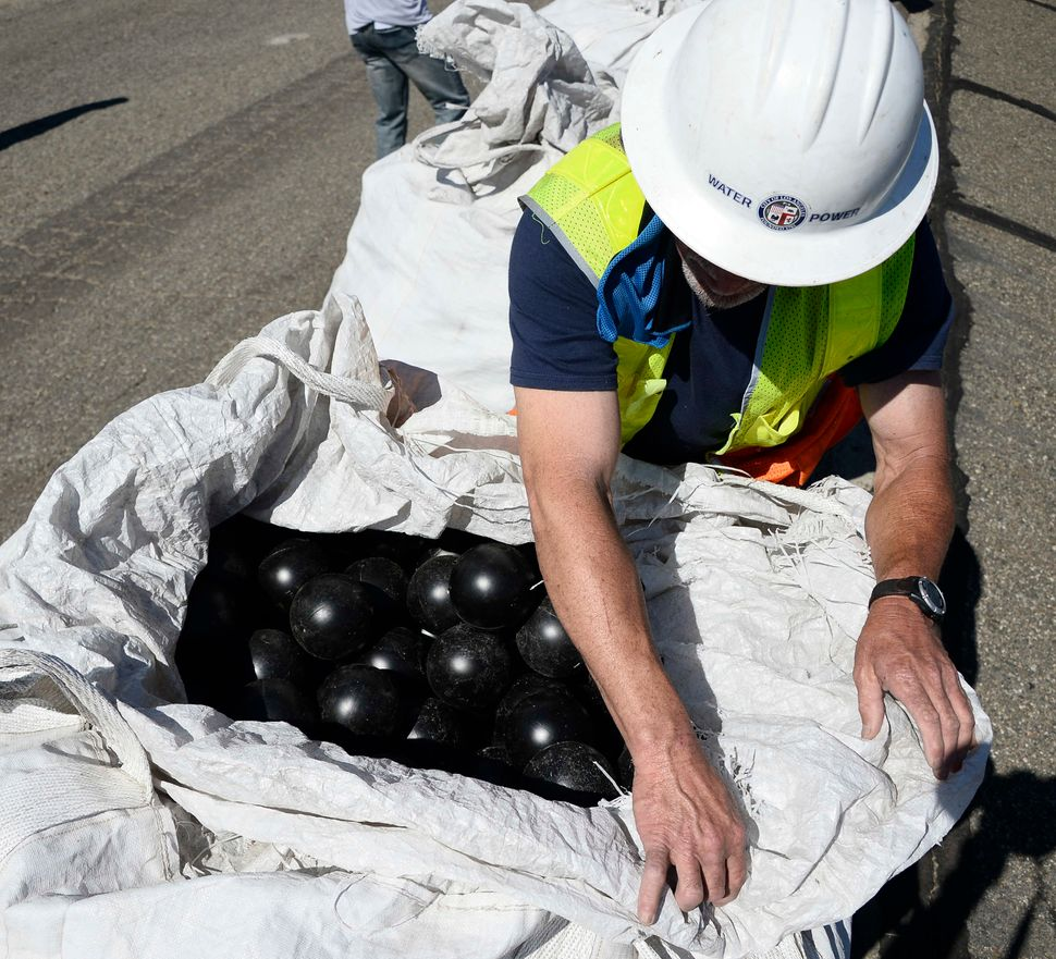An employee of the Los Angeles Department of Water and Power opens a bag of shade balls.